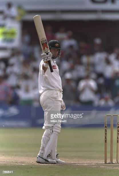 Mark Waugh of Australia holds up his bat after reaching 100 runs during the second test match against South Africa at Port Elizabeth South Africa...