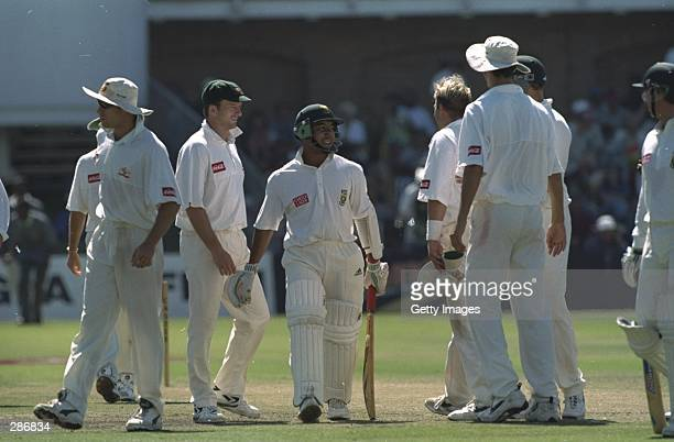 Paul Adams of South Africa has a word with the Australian bowler Shane Warne after he was caught out reverse sweeping during the second test match at...