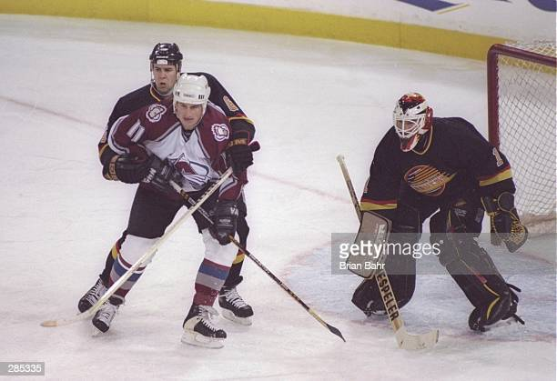 Right wing Keith Jones of the Colorado Avalanche tries to free himself from the hands of defensemen Adrian Aucoin of the Vancouver Canucks as fellow...