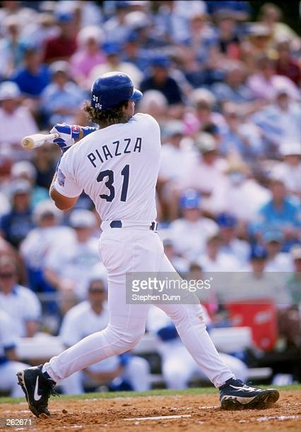 Catcher Mike Piazza of the Los Angeles Dodgers signs autographs during a spring training game against the New York Mets at the Holman Stadium in Vero...