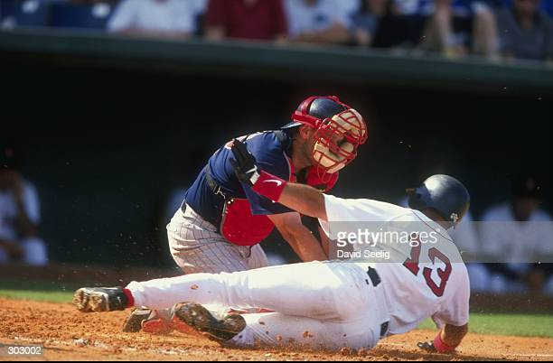 Infielder John Valentin of the Boston Red Sox slides into home as catcher Terry Steinbach of the Minnesota Twins tries to tag him out during a spring...