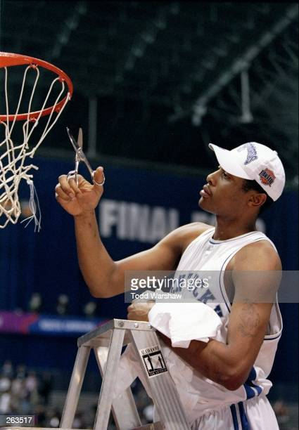 Jamaal Magloire of the Kentucky Wildcats celebrates a victory over the Utah Utes by cutting down the net during the final game of the NCAA...