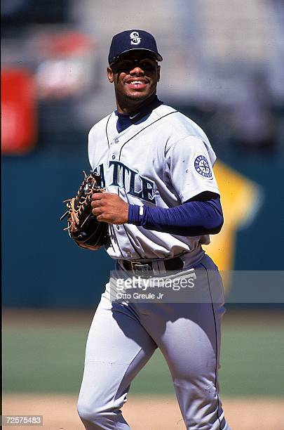 Ken Griffey Jr #24 of the Seattle Mariners smiles and looks on from the field during the game against the Oakland Athletics at the Oakland Coliseum...