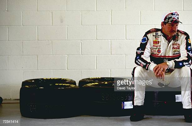 Dale Earnhardt sitting on some tires looking on during practice for the Las Vegas 400 of the NASCAR Winston Cup Series at the Las Vegas Motor...