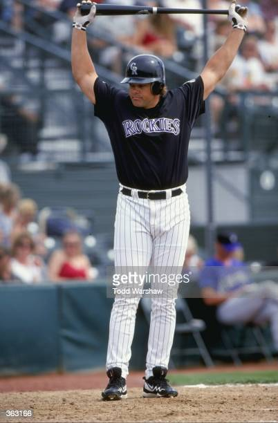 Dante Bichette of the Colorado Rockies stretches as he walks to the plate during a Spring Training game against the Arizona Diamondbacks at the Hi...