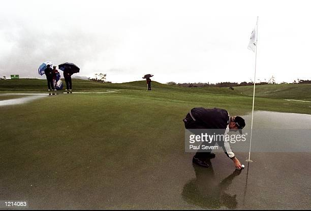 Gary Evans of England marks his ball on a waterlogged green during the Madeira Island Open at the Santo Da Serra GC in Madeira Spain Mandatory Credit...