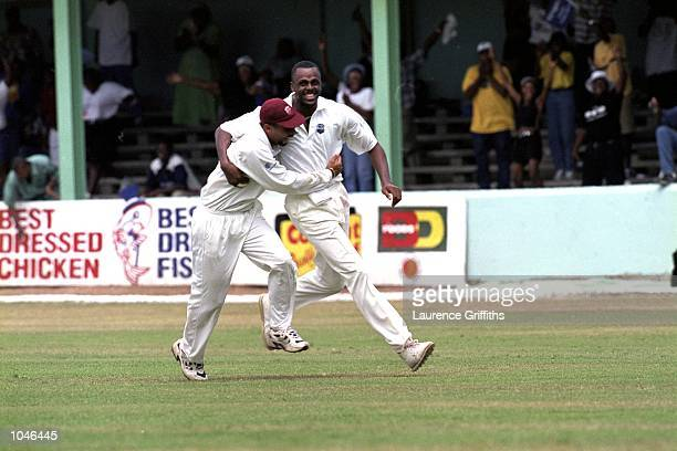 Courtney Walsh of the West Indies celebrates with Jimmy Adams as he has Henry Olonga caught by Wavell Hinds to claim his 435th wicket breaking Kapil...