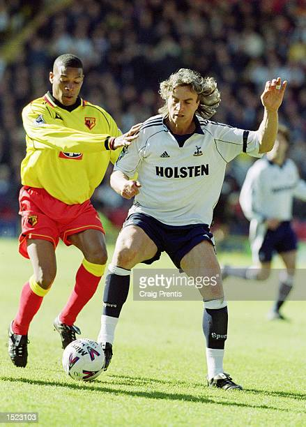 David Ginola of Tottenham Hotspur holds off Micah Hyde of Watford during the FA Carling Premiership match at Vicarage Road in Watford England The...