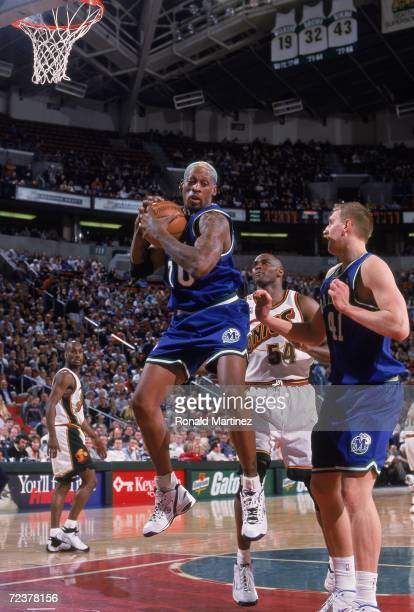 Dennis Rodman of the Dallas Mavericks rebounds the ball during a game against the Seattle SuperSonics at the Key Arena in Seattle Washington The...