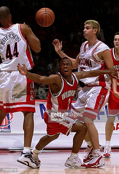 Guard Travon Davis of the Wisconsin Badgers tries to maintain control of the ball against forwards Richard Jefferson and Rick Anderson of the Arizona...