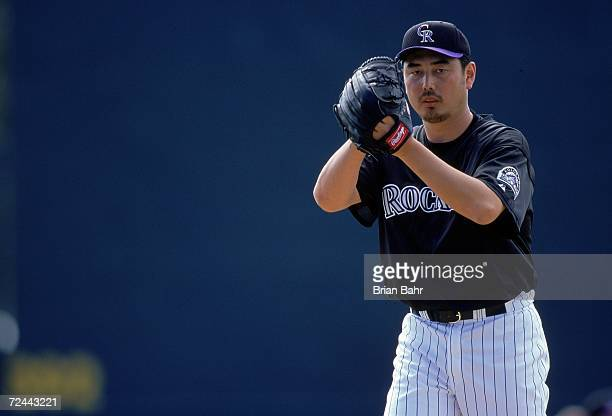 Pitcher Masato Yoshii of the Colorado Rockies starts the windup during the Spring Training Game against the Milwaukee Brewers at Hi Corbett Field in...