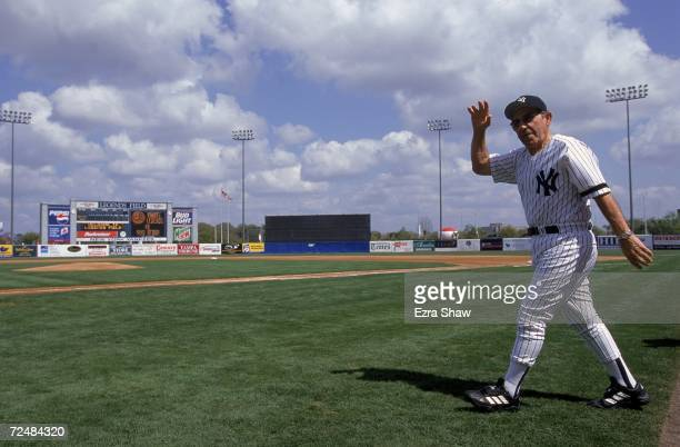 Yogi Berra of the New York Yankees waves to the crowd as he walks out onto the field during the Spring Training Game against the Toronto Blue Jays at...