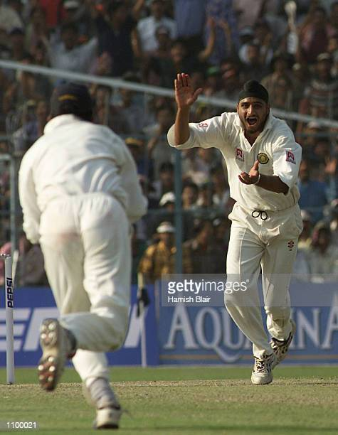 Harbhajan Singh of India claims the wicket of Shane Warne of Australia to complete a hat trick during day one of the 2nd Test between India and...