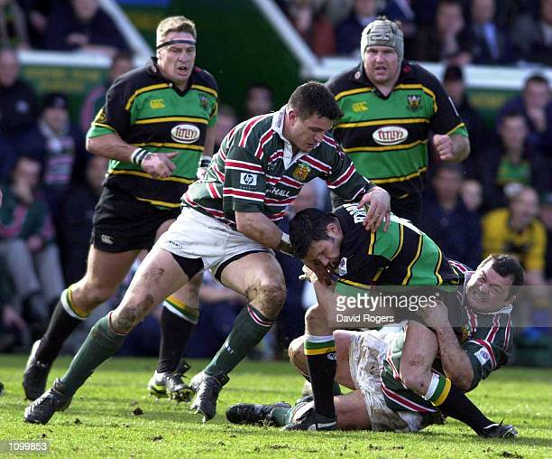 James Brookes of Northampton Saints is tackled by Martin Corry and Darren Garforth of Leicester Tigers during the Zurich Premiership match between...