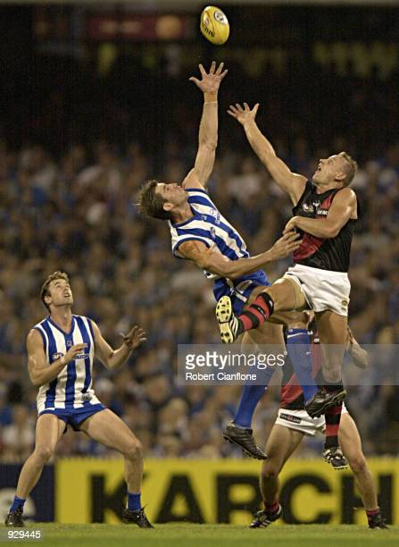 John Barnes of Essendon and Corey McKernan of the Kangaroos in action during a ruck duel in the match between the Kangaroos and the Essendon Bombers...