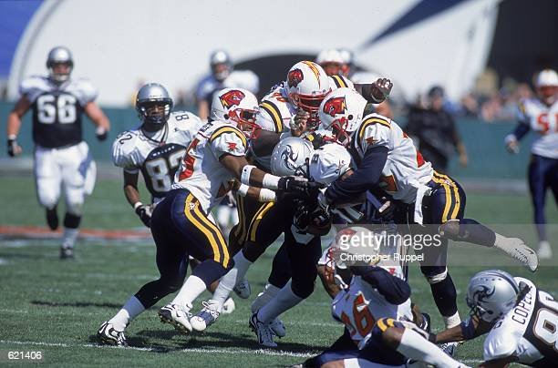 Kelly Malveaux of the Orlando Rage makes the tackle with Stephen Fisher and Damon Gibson against the Los Angeles Xtreme at the Los Angeles Coliseum...