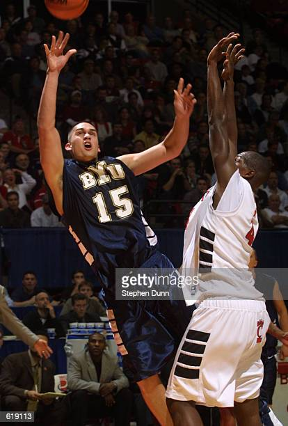 Mekeli Wesley of Brigham Young University shoots over BJ Grove of Cincinnati during the first round of the Men's NCAA Tournament at Cox Arena in San...