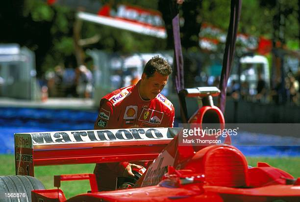 Michael Schumacher of Germany and the Marlboro Ferrari Formula one team surveys the damage to his car after walking away from a massive crash during...