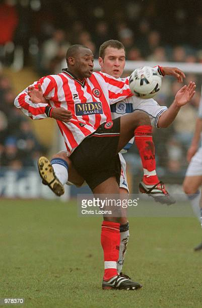 Peter Ndlouvu of Sheffield United is tackled by Mark Perry of Queens Park Rangers during the Nationwide First Division match between Queens Park...