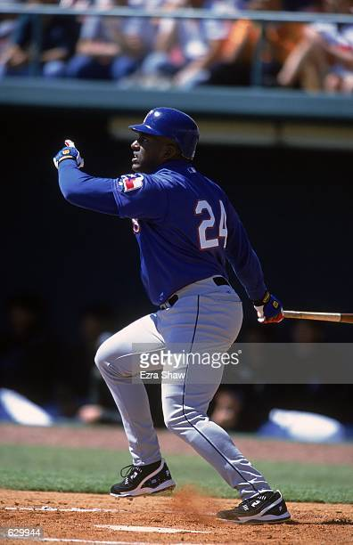 Ruben Sierra of the Texas Rangers keeps his eye on the ball after hitting it during the Spring Training Game against the Tampa Bay Devil Rays at...