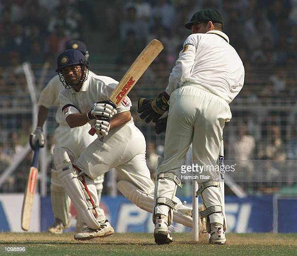 Sachin Tendulkar of India sweeps off the bowling of Shane Warne of Australia with wicketkeeper Adam Gilchrist looking on during day three of the...