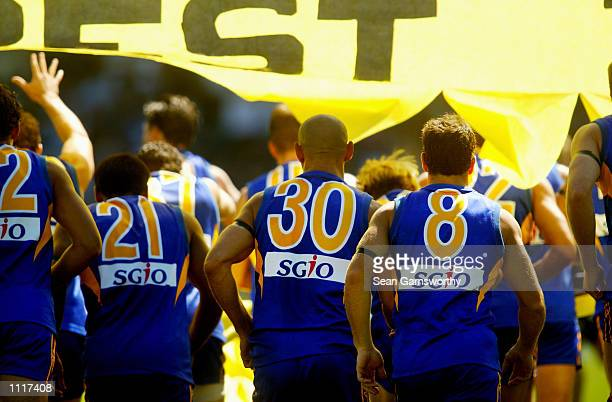 The West Coast team run through the banner before the round 1 AFL football match between the West Coast Eagles and Fremantle Dockers at Subiaco Oval...