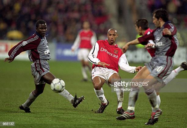 Thierry Henry of Arsenal plays the ball past Samuel Kuffour of Bayern Munich during the UEFA Champions League Group C match at the Olympiastadion in...