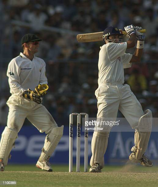 VVS Laxman of India hits out on his way to a century with Adam Gilchrist of Australia looking on during day three of the 2nd Test between India and...