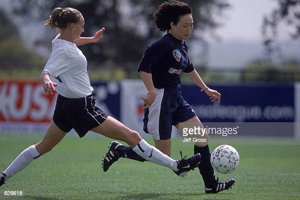 Wen Lirong of the Carolina Courage kicks the ball away from Krista Davey of the DC Freedom during the Spring Training game at the Arco Olympic...