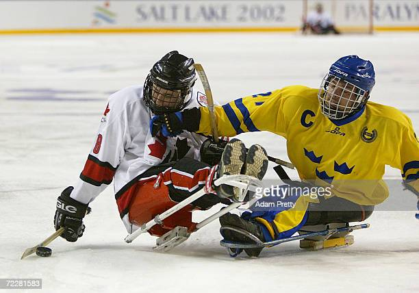 Billy Bridges of Canada is tackeled by Marcus Holm of Sweden during the Canada and Sweden Bronze Medal Sledge Hockey match which Sweden won in sudden...