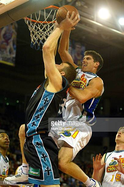 Brett Wheeler for the Titans rebounds under pressure from Mike Kelly for the Crocs during the NBL match between the Victorian Titans and the...