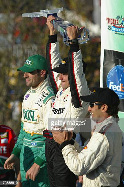 Cristiano Da Matta of the Newman-Haas Racing Team lifts the winner's trophy after winning ahead of second place finisher Dario Franchitti and third...