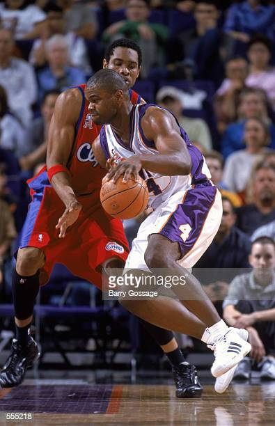Forwad Alton Ford of the Phoenix Suns dribbles the ball around center Michael Olowokandi of the Los Angeles Clippers during the NBA game at the...