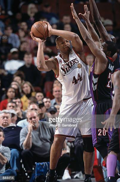 Forward Derrick Coleman of the Philadelphia 76ers looks to pass the ball under defensive pressure by Guard Alvin Williams of the Toronto Raptors...