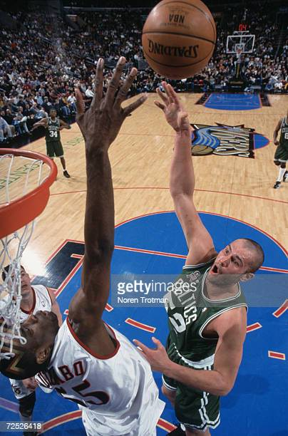 Forward Vitaly Potapenko of the Boston Celtics shoots the ball over center Dikembe Mutombo of the Philadelphia 76ers during the NBA game at the First...