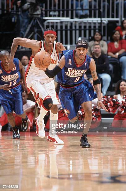 Guard Allen Iverson of the Philadelphia 76ers dribbles the ball as foward DerMarr Johnson of the Atlanta Hawks chases Iverson during the NBA game at...