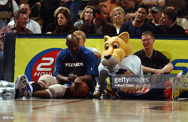 Guard Michael Jordan of the Washington Wizards signs an autograph for mascot Rocky of the Denver Nuggets during the NBA game at the Pepsi Center in...