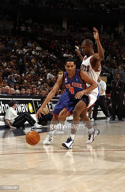 Howard Eisley of the New York Knicks drives past Calbert Cheaney of the Denver Nuggets during their game at Pepsi Center in Denver Colorado The...