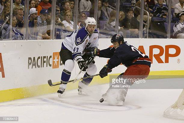 Jason Allison of the Los Angeles Kings fights for the puck with Tyler Wright of the Columbus Blue Jackets during the game at Staples Center in Los...