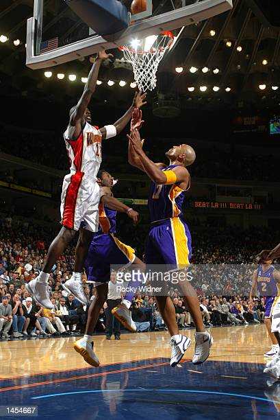 Jason Richardson of the Golden State Warriors shoots over Kobe Bryant and Rick Fox of the Los Angeles Lakers at The Arena in Oakland California...