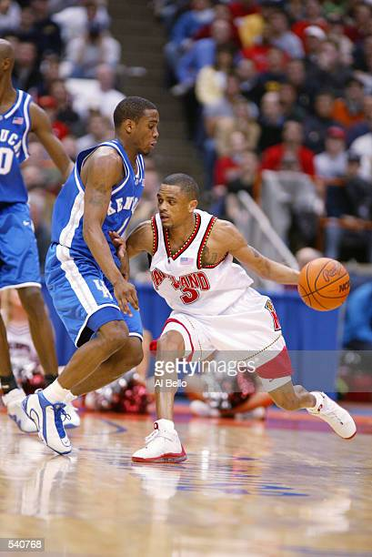 Juan Dixon of Maryland moves against the defense of Cliff Hawkins of Kentucky during the East Regional Semi Final at the Carrier Dome in Syracuse New...