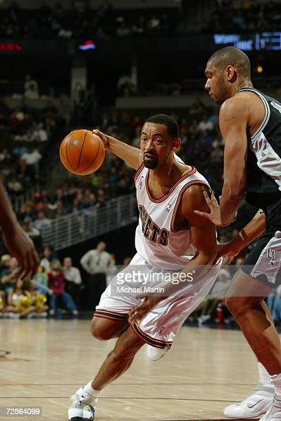Juwan Howard of the Denver Nuggets drives in against Tim Duncan of the San Antonio Spurs during their game at Pepsi Center in Denver Colorado The...