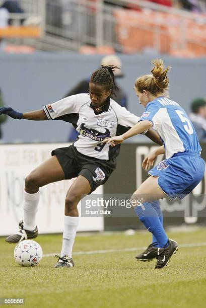 Katia of the San Jose Cyberrays maneuvers the ball against Carrie Moore of the Washington Freedom during the WUSA game at Mile High Stadium in...