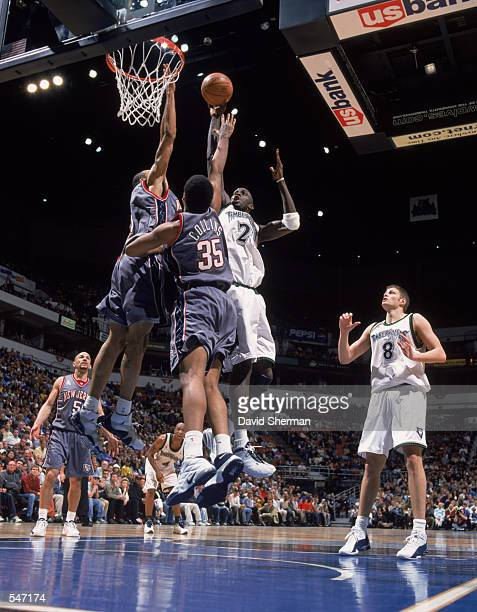 Kevin Garnett#21 of the Minnesota Timberwolves tries for a basket as he is blocked by Jason Collins and Kenton Martin of the New Jersey Nets during...