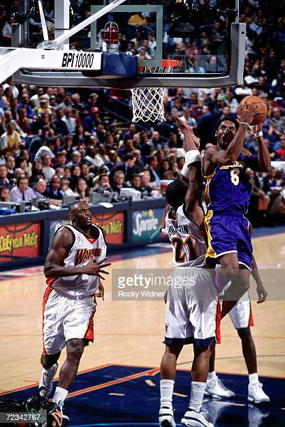 Kobe Bryant of the Los Angeles Lakers drives to the basket for a layup against the Golden State Warriors during the NBA Game at The Arena In Oakland...
