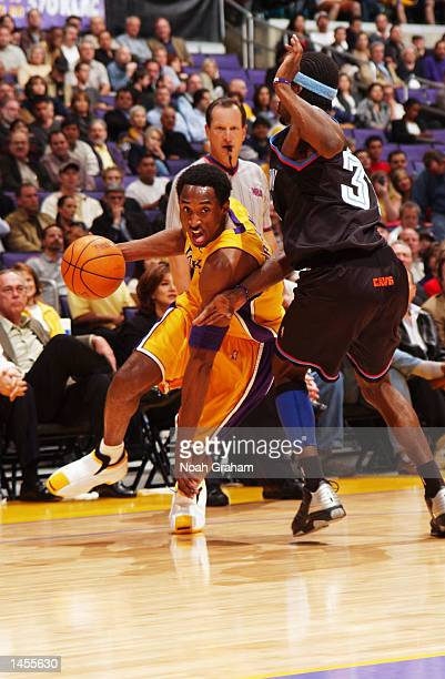 Kobe Bryant of the Los Angeles Lakers tries to get to the basket past Ricky Davis of the Cleveland Cavaliers during the first half of action at...