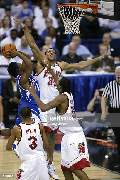 Lonny Baxter of Maryland defends a shot by Bryant Nash of Kansas during the semifinal round of the NCAA Men's Final Four at the Georgia Dome in...