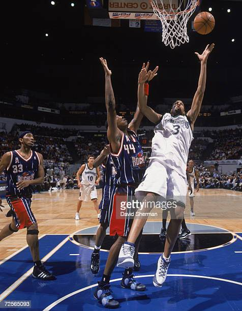 Loren Woods of the Minnesota Timberwolves jumps to make a basket as he is blocked Terence Morris of the Houston Rockets during the game at the Target...
