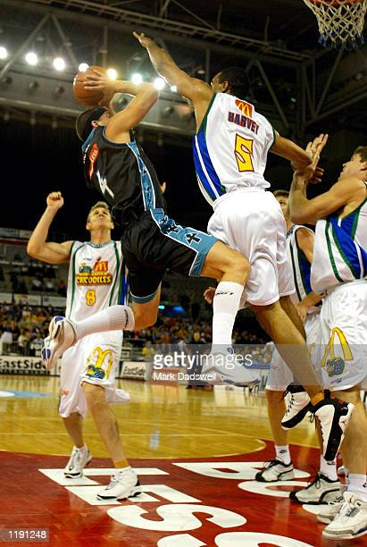 Mark Dickel for the Titans drives to the basket as Shawn Harvey for the Crocs during the NBL match between the Victorian Titans and the Townsville...