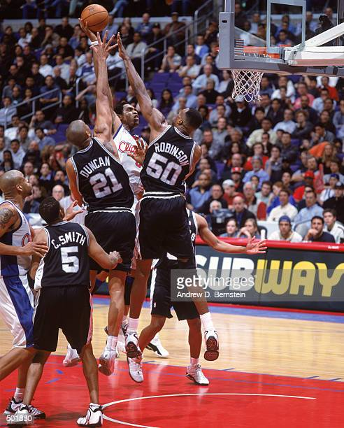 Michael Olowokandi of the Los Angeles Clippers leaps to make the basket as he is blocked by David Robinson and Tim Duncan of the San Antonio Spurs at...